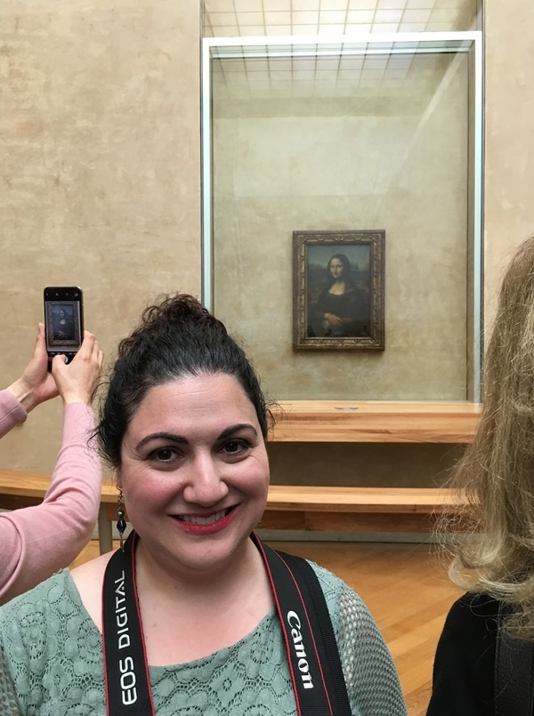 a woman posing in front of the Mona Lisa
