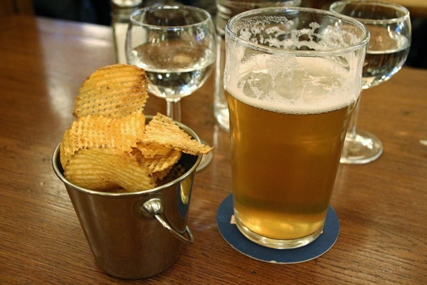 A glass of beer on a table next to a bowl of potato chips