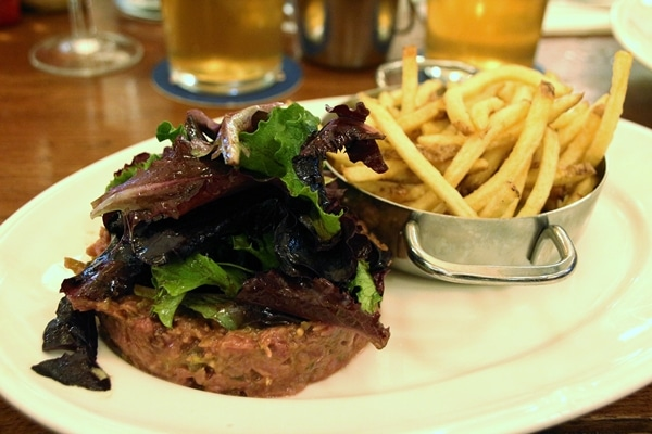 A close up of steak tartare with salad and fries on a white plate