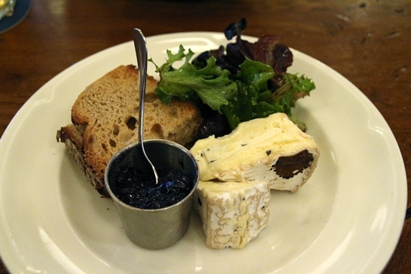 2 pieces of soft cheese with jam, bread, and greens
