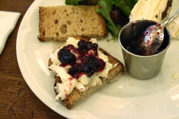a piece of bread topped with soft cheese and fruit jam