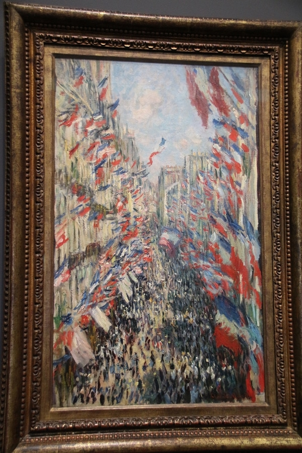 a painting of French flags hanging over a crowd of people in the street