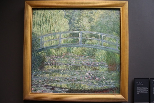 A painting of a bridge over a pond of lilies