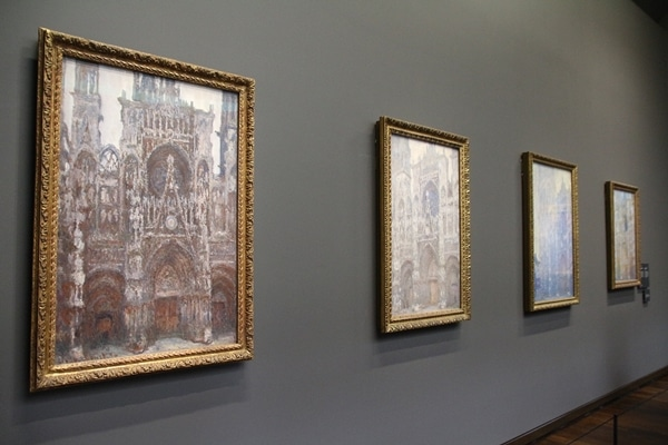 a row of paintings on a gray wall