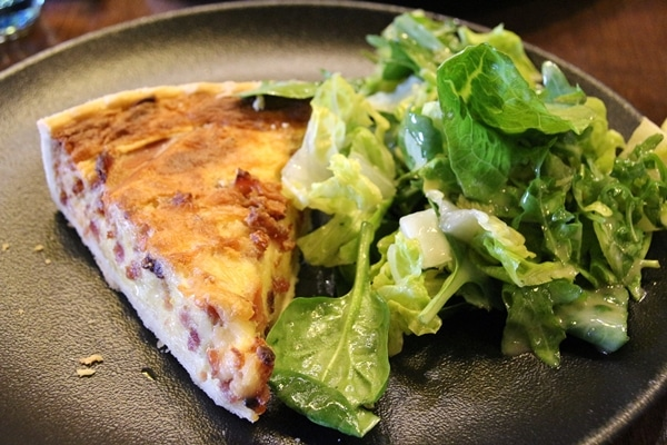 a wedge of quiche with salad on a dark plate