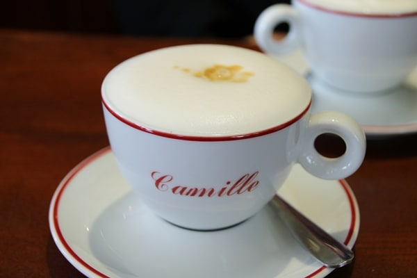 cappuccino in a white and red cup that says Camille