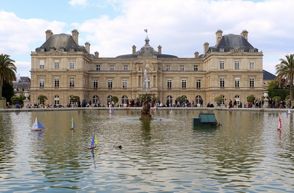 A group of people around a fountain in front of Luxembourg Palace