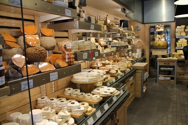 a variety of cheeses on display in a shop