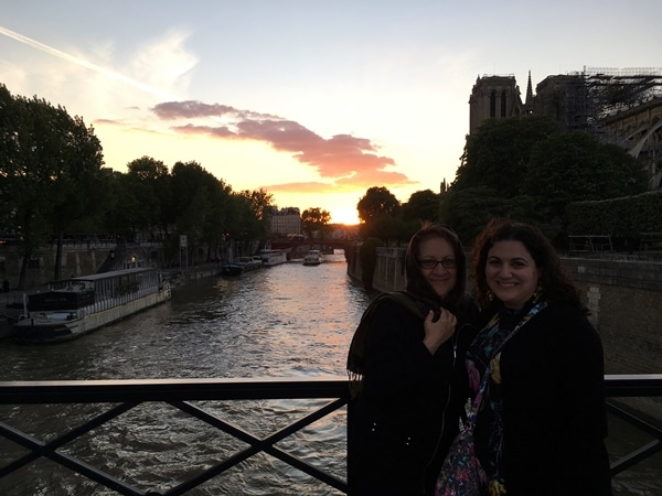 2 women on a river bridge at sunset