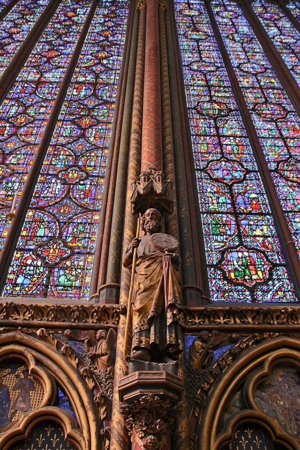 statue of an apostle beneath tall stained glass windows