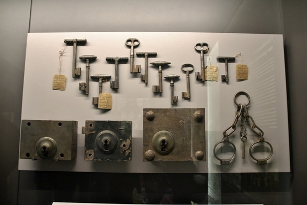 a bunch of old keys and locks in a museum display