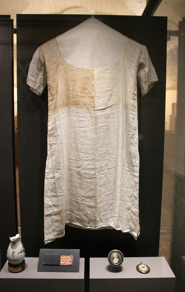 an old stained frock in a museum display
