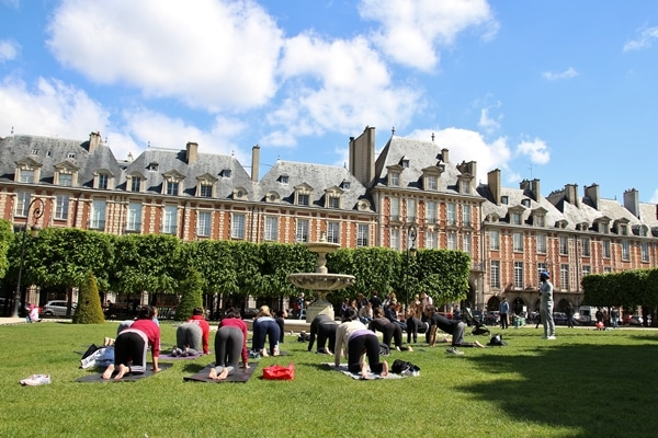 A group of people doing yoga in the grass at Place des Vosges in Paris