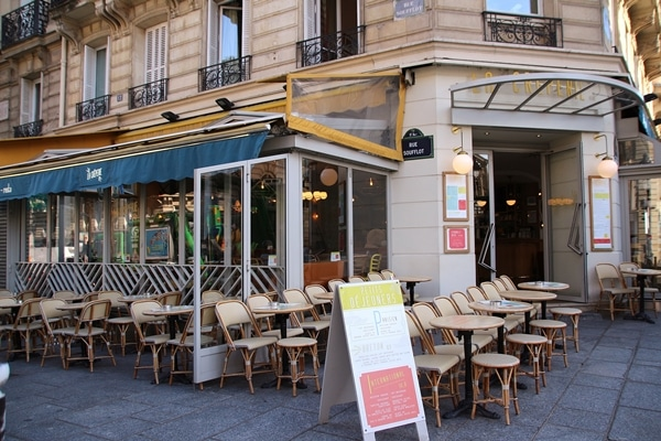 exterior of a Parisian restaurant with small tables and chairs