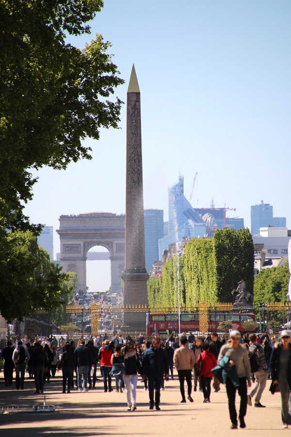 an obelisk with the Arc de Triomphe in the distance