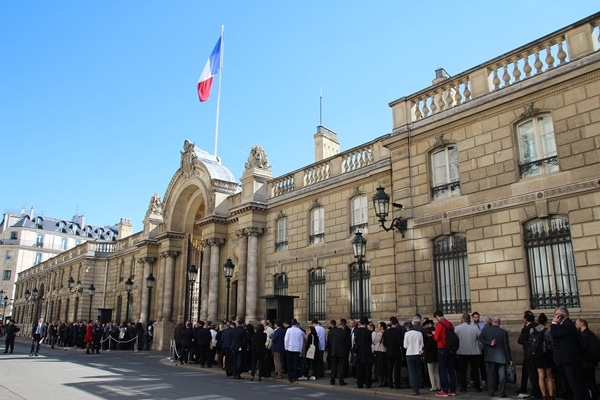 A group of people standing in front of Élysée Palace