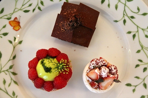 3 beautifully decorated desserts on a white plate