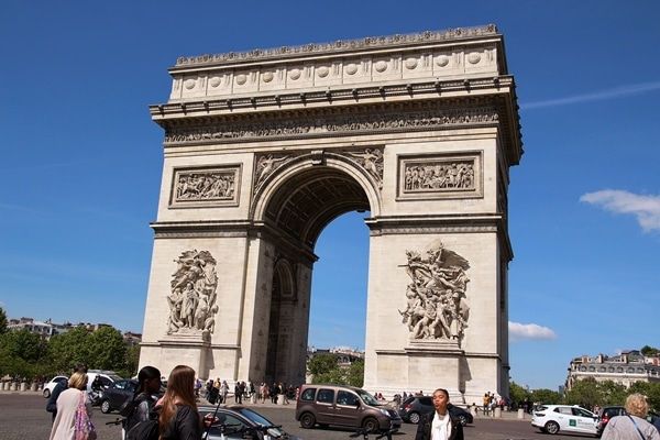 A group of people standing in front of Arc de Triomphe