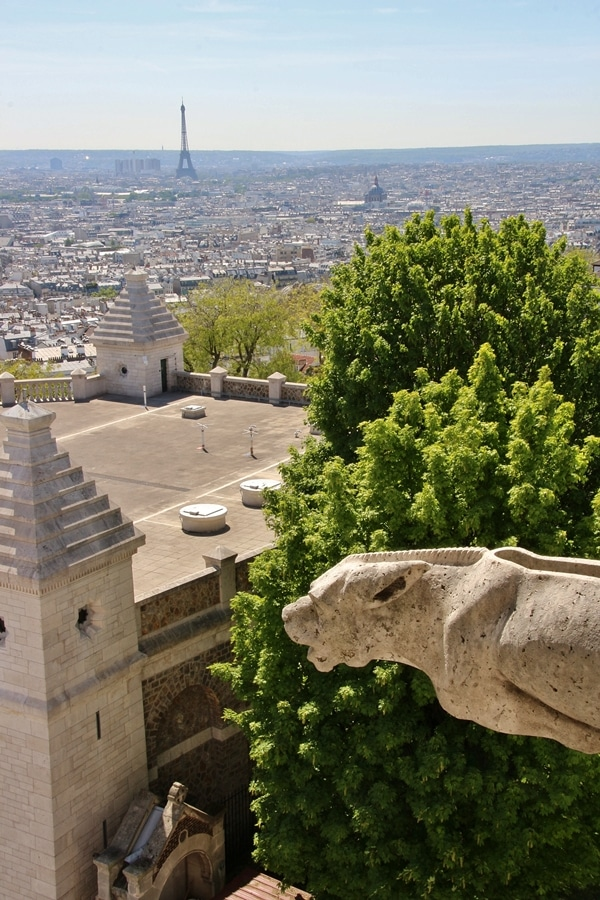 a gargoyle with Paris in the distance