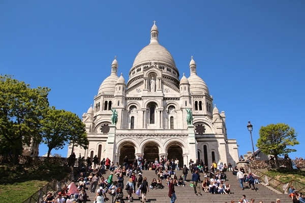 A group of people standing in front of Sacré-Cœur Basilica in Paris