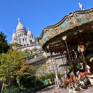 Sacre Coeur Basilica in Paris France with carousel in foreground