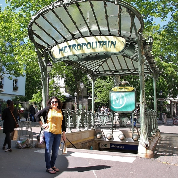 a woman standing in front of an ornate Parisian metro sign