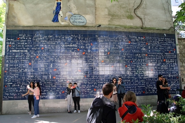 groups of people standing in front of a blue wall with writing