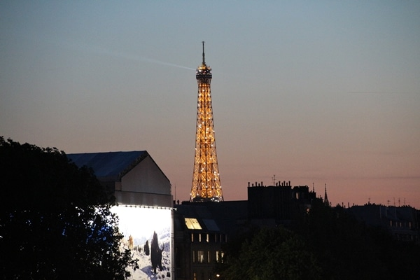 the Eiffel Tower in the distance lit up at night
