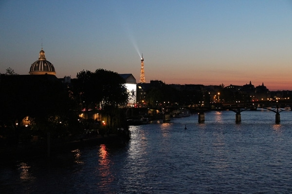 nighttime view of the River Seine and Eiffel Tower in the distance