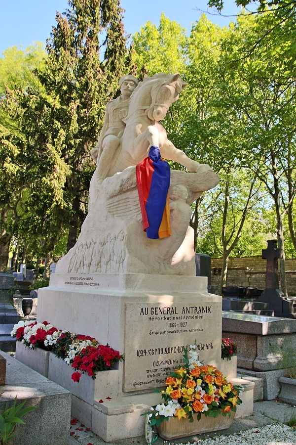 a monumental grave with an Armenian flag in a cemetery