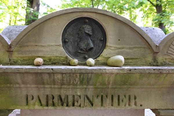 A closeup of Parmentier\'s grave with potatoes on it