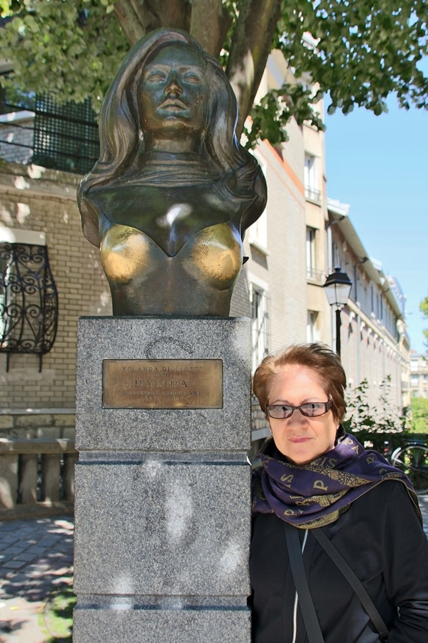a woman posing with a statue of Dalida