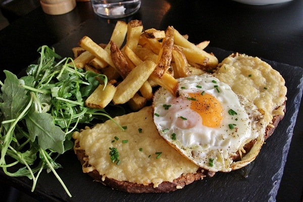 a croque madame sandwich with fries and salad on a black surface