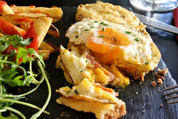 A close up of a croque madame sandwich with a few pieces cut off