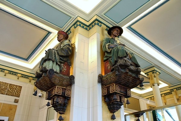 2 statues of Chinese men on either side of a column