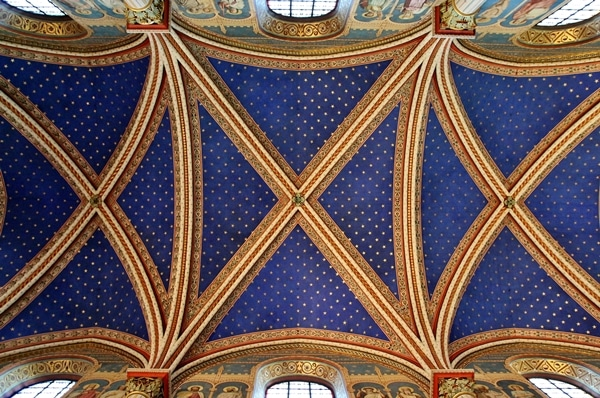 view looking up at a vaulted church ceiling painted blue with gold embellishments