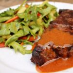 Boma mustard sauce served over steak with side of salad