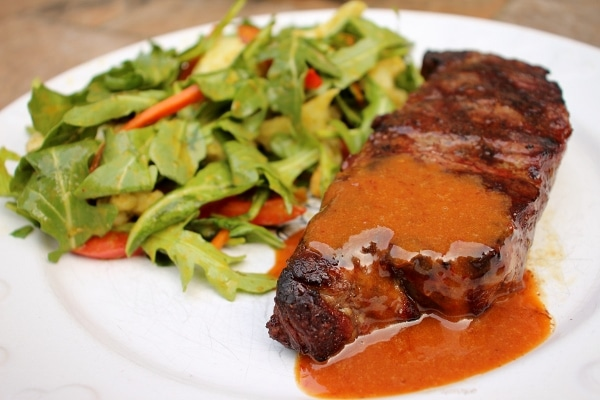 steak topped with a reddish sauce on a white plate
