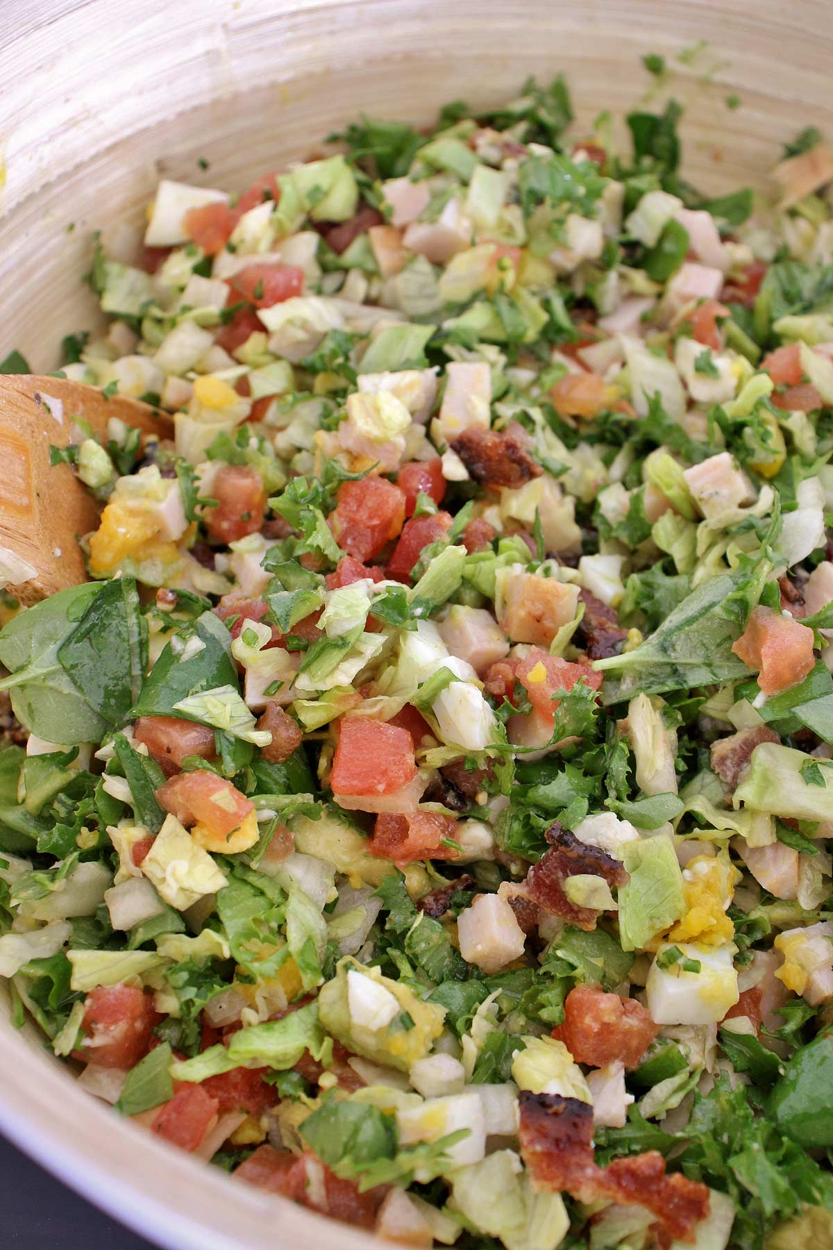 Closeup of tossed Cobb Salad in a wooden mixing bowl.