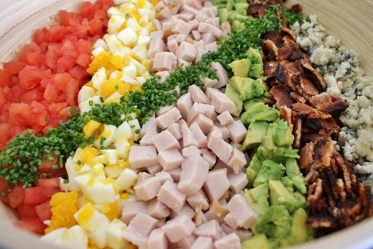 Closeup of Cobb salad with rows of colorful ingredients on top.
