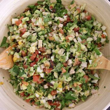 Tossed Hollywood Brown Derby Cobb Salad in a wooden mixing bowl with 2 wooden spoons.