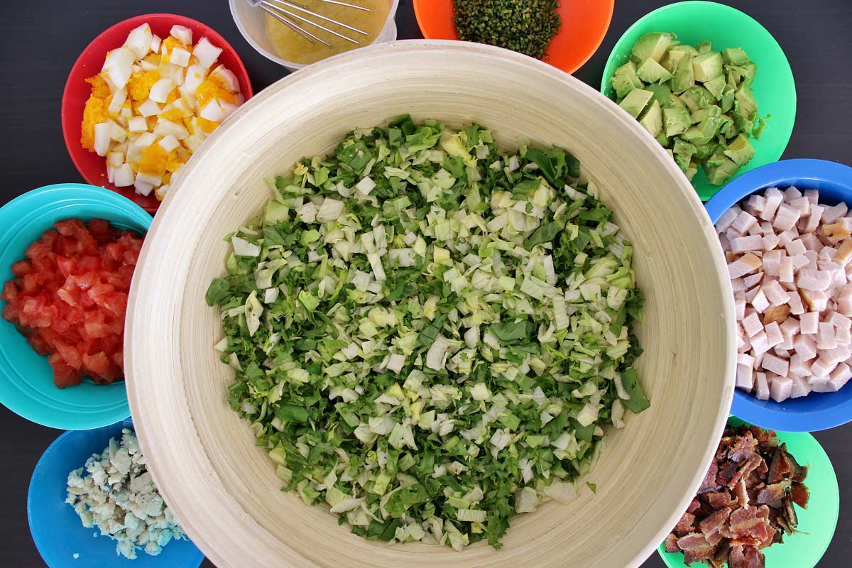 Chopped greens in a large salad bowl surrounded by smaller bowls of toppings for Cobb salad.