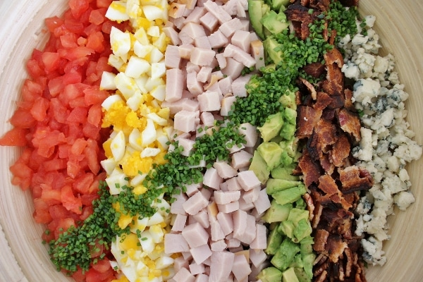 Hollywood Brown Derby Cobb Salad before tossing. Vertical rows of salad toppings from left to right include tomatoes, hard-boiled eggs, chopped turkey, avocado, bacon, and blue cheese. A diagonal line of minced chives covers the surface.