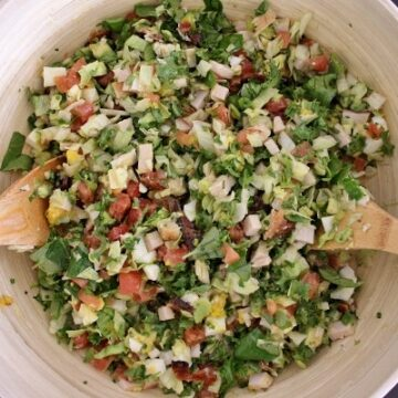 Hollywood Brown Derby Cobb Salad tossed together in a large wooden bowl