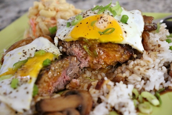 beef patty topped with egg, cut in half with runny egg yolk dripping down