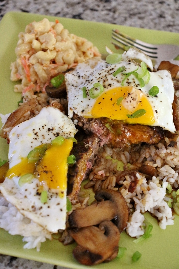 White rice topped with a beef patty, mushroom gravy, and a fried egg, cut in half