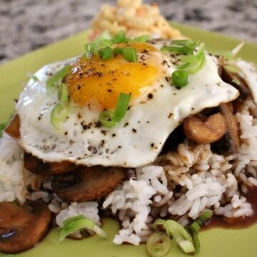 Loco moco, rice topped with beef patty, gravy, and fried egg served with macaroni salad