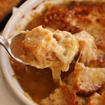 closeup of a spoonful of French onion soup with a crouton and melted cheese