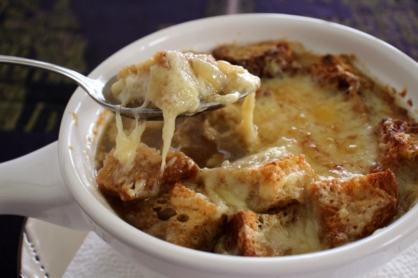 A spoonful of French onion soup with melted cheese stretching from the bowl