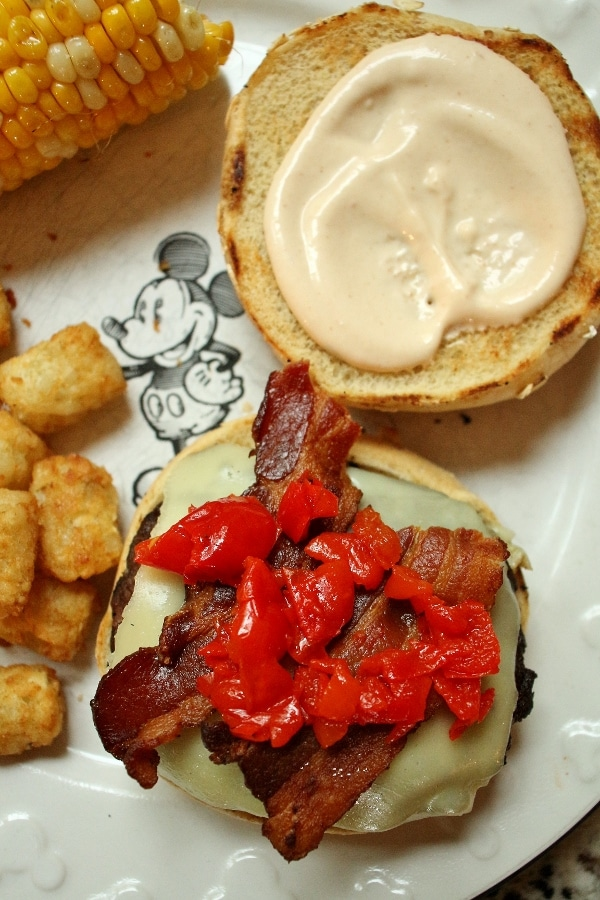 a cheeseburger with crispy bacon and cherry peppers on top